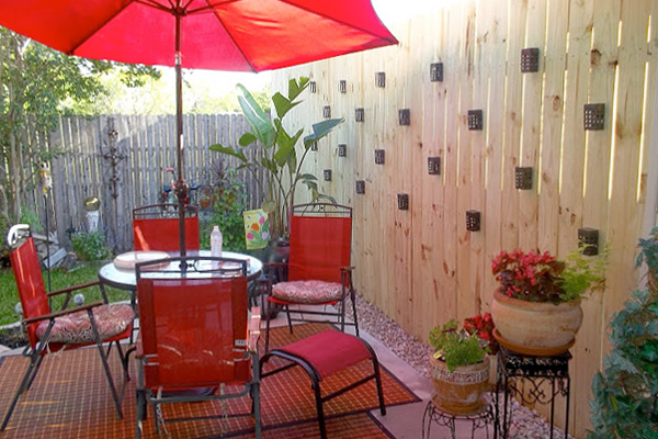 Patio set in back yard of house next to tall privacy fence